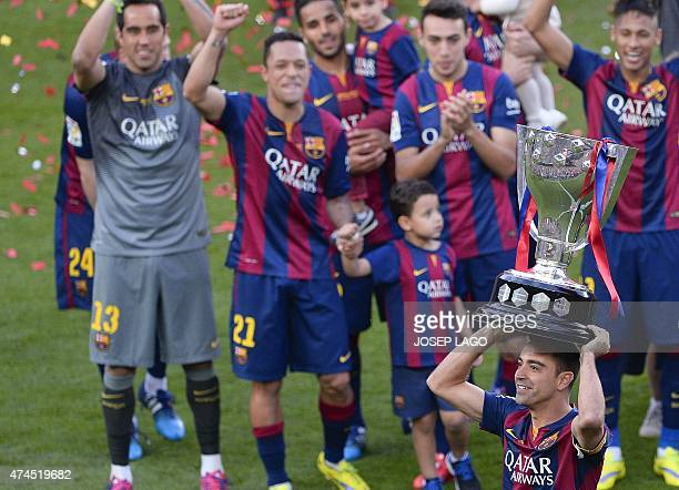 Barcelona's midfielder Xavi Hernandez holds the Spanish League 2014/15 trophy after winning the Spanish league football match FC Barcelona vs RC...