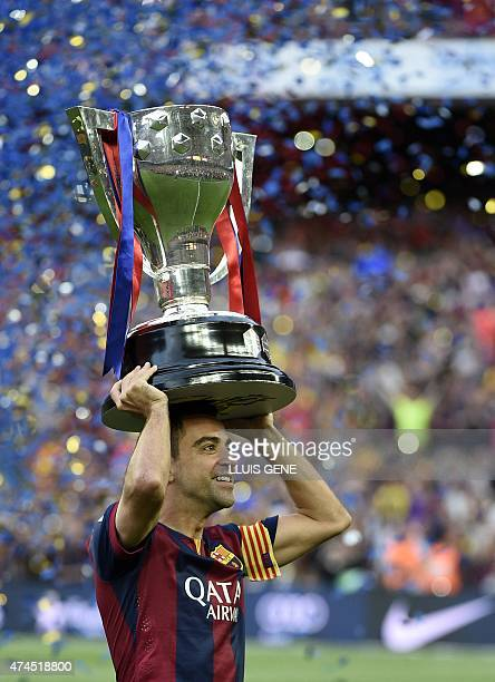 Barcelona's midfielder Xavi Hernandez holds up the trophy for the Spanish league title of 2014/15 after the Spanish league football match FC...