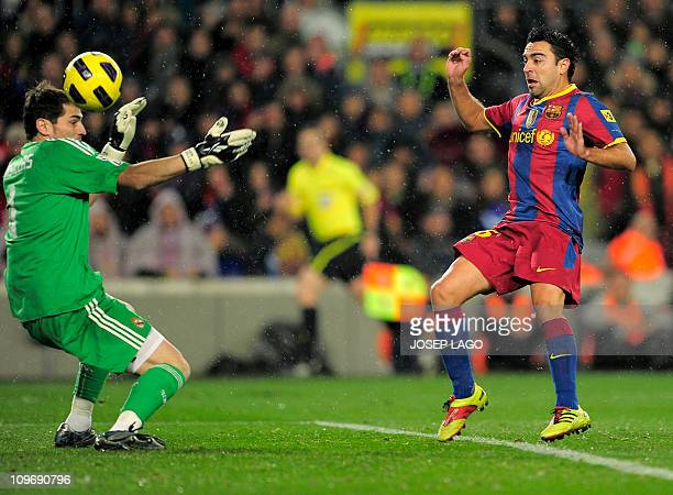 Barcelona's midfielder Xavi Hernandez scores his team's first goal to Real Madrid's goalkeeper and captain Iker Casillas during the Spanish league...