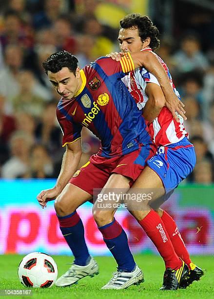 Barcelona's midfielder Xavi Hernandez vies with Sporting Gijon's midfielder Miguel De Las Cuevas during their Spanish League football match Barcelona...