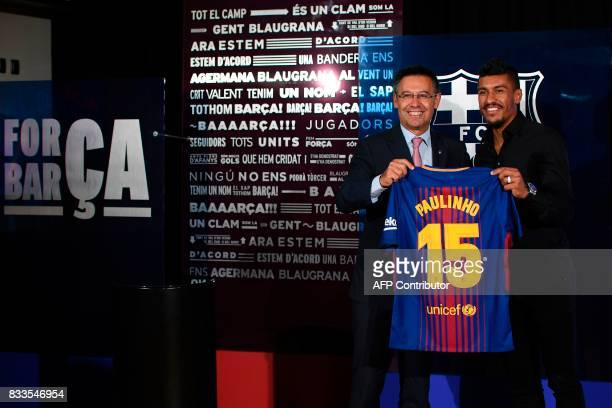 Barcelona's new Brazilian football player Paulinho Bezerra poses with his new jersey and Barcelona's president Josep Maria Bartomeu during his...
