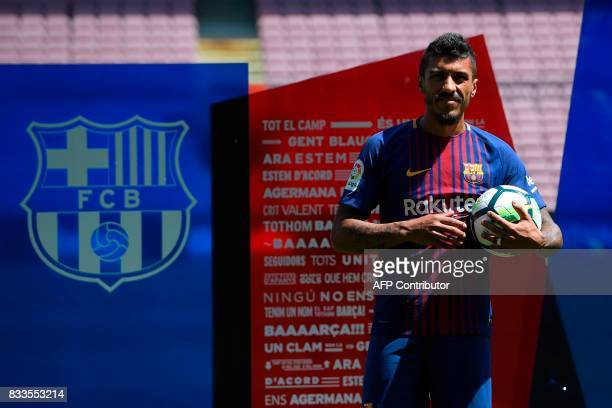 Barcelona's new Brazilian football player Paulinho Bezerra poses with a ball on the pitch during his official presentation after signing his new...