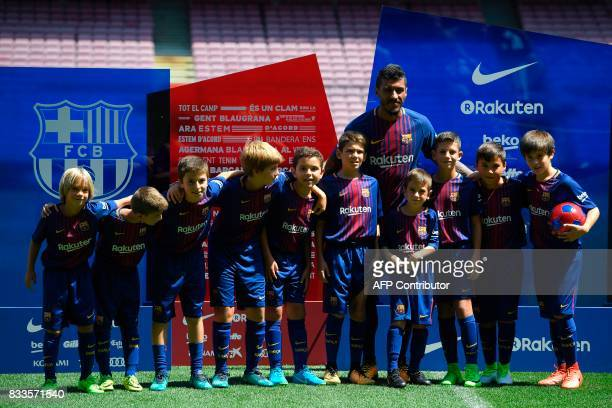 Barcelona's new Brazilian football player Paulinho Bezerra poses with young Barcelona's fans during his official presentation after signing his new...