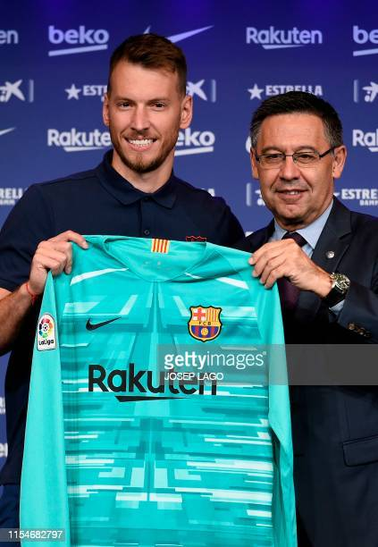 Barcelona's new Brazilian goalkeeper Neto poses with his new jersey next to the Spanish club's president Josep Maria Bartomeu during his official...