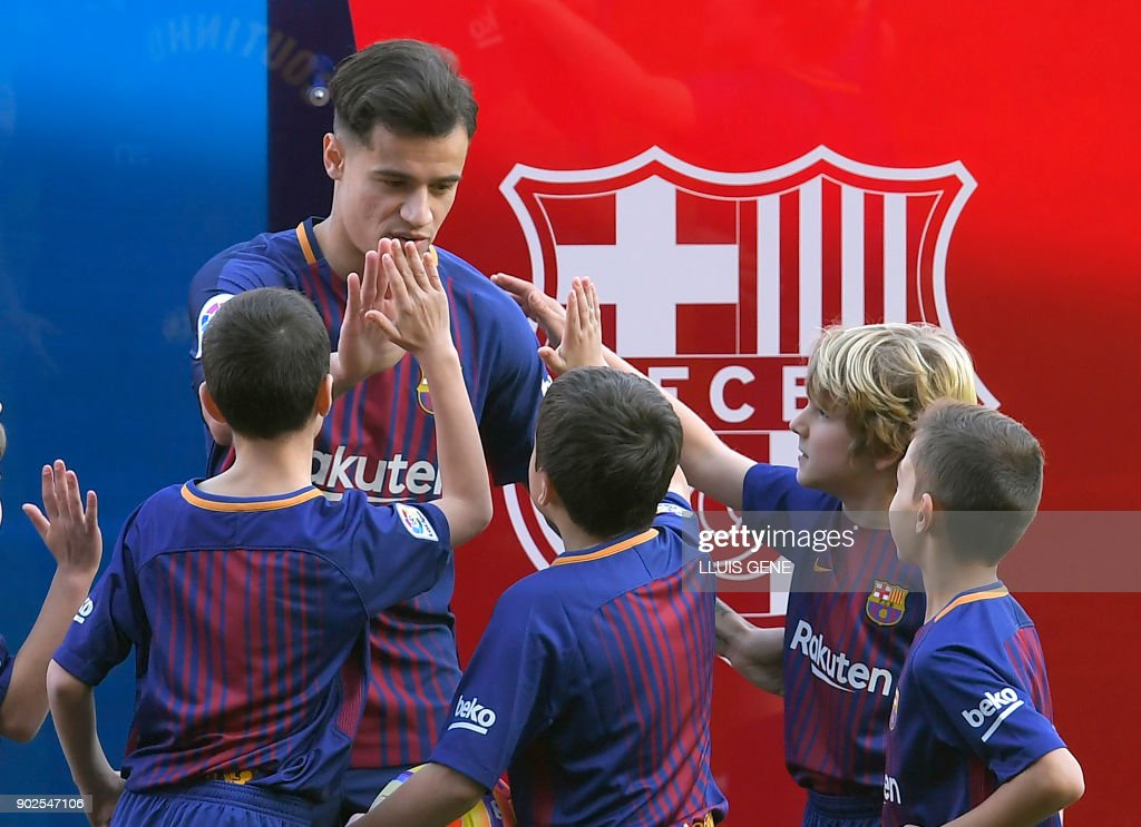 Barcelona's new Brazilian midfielder Philippe Coutinho cheers some children as he poses with his new jersey during his official presentation in Barcelona on January 8, 2018. Philippe Coutinho officially joined Barcelona today, completing a move from Liverpool thought to be worth 160 million euros ($192 million), making it the third richest transfer in history. GENE