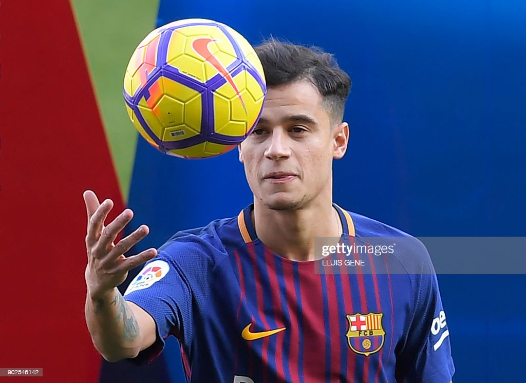 Barcelona's new Brazilian midfielder Philippe Coutinho plays with a ball as he poses with his new jersey during his official presentation in Barcelona on January 8, 2018. Philippe Coutinho officially joined Barcelona today, completing a move from Liverpool thought to be worth 160 million euros ($192 million), making it the third richest transfer in history. GENE