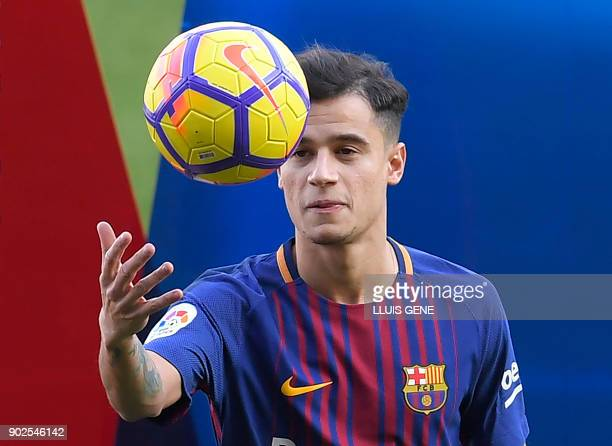 Barcelona's new Brazilian midfielder Philippe Coutinho plays with a ball as he poses with his new jersey during his official presentation in...