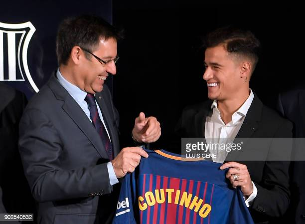 Barcelona's new Brazilian midfielder Philippe Coutinho poses with his new jersey beside Barcelona FC President Josep Maria Bartomeu during his...