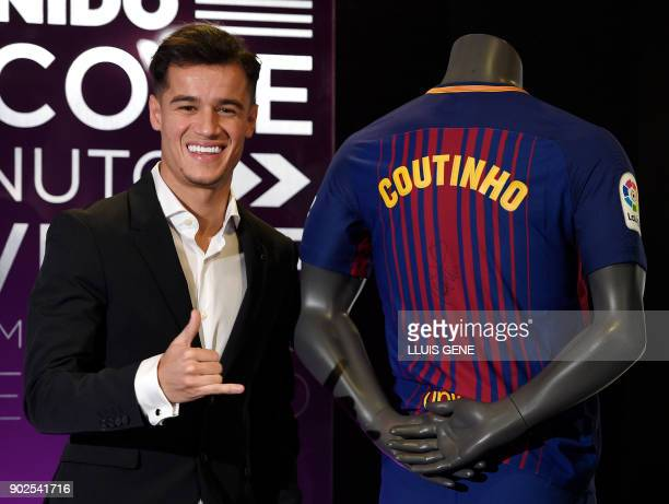 Barcelona's new Brazilian midfielder Philippe Coutinho poses with his new jersey during his official presentation in Barcelona on January 8 2018...