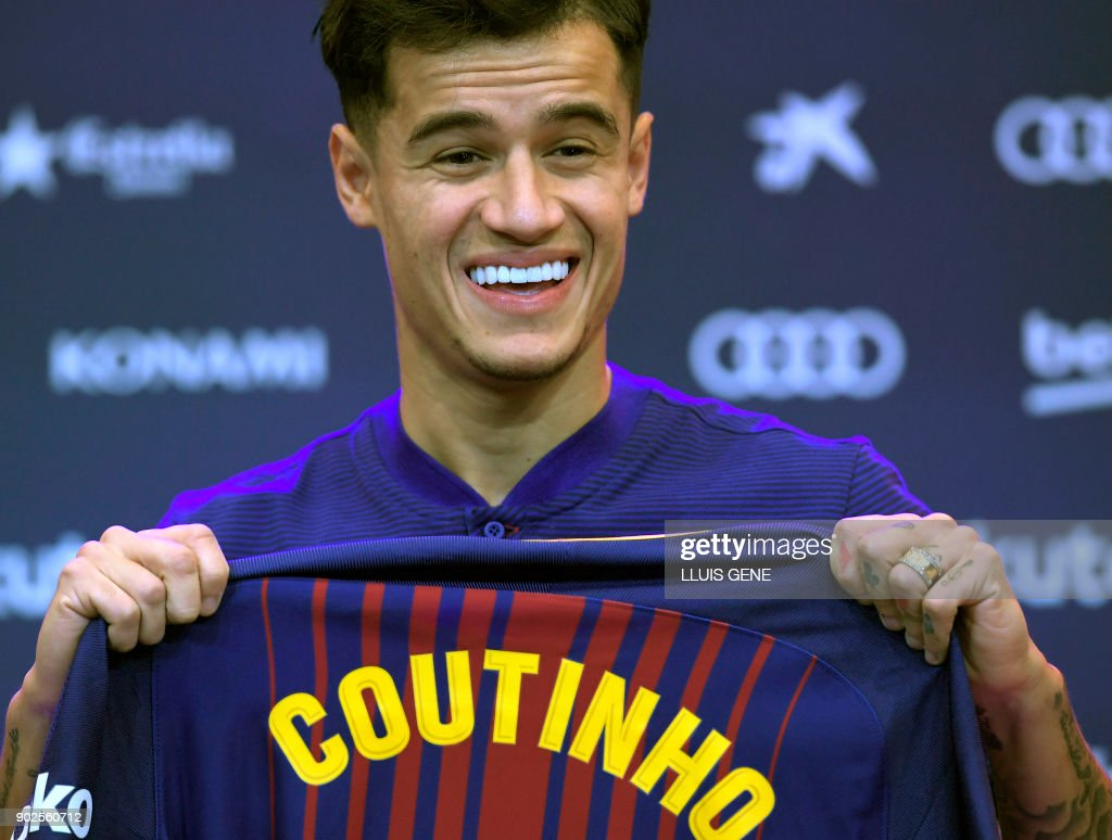 TOPSHOT - Barcelona's new Brazilian midfielder Philippe Coutinho shows his new jersey before holding a press conference in Barcelona on January 8, 2018. Philippe Coutinho officially joined Barcelona today, completing a move from Liverpool thought to be worth 160 million euros ($192 million), making it the third richest transfer in history. /
