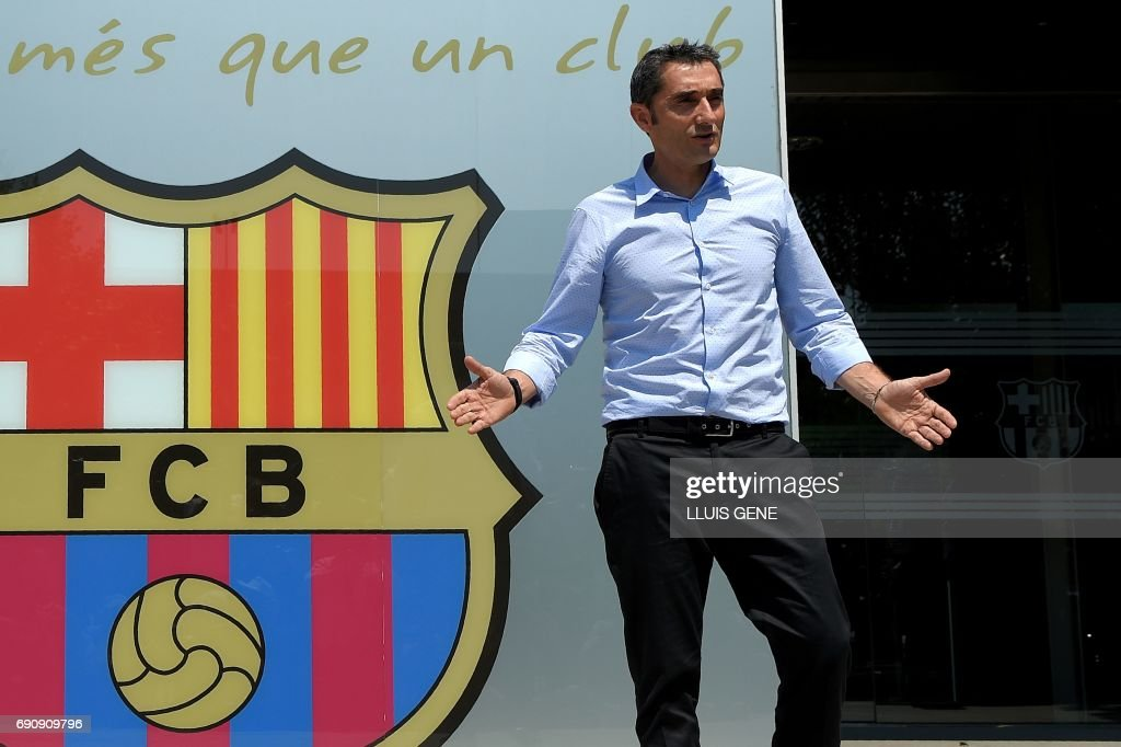 Barcelona's new coach Ernesto Valverde gestures as he poses outside the Camp Nou stadium in Barcelona on May 31, 2017 prior to signing his new contract with the Catalan club. /