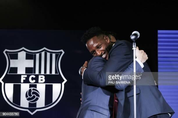 Barcelona's new Colombian defender Yerry Mina hugs Barcelona football club president Josep Maria Bartomeu during his official presentation in...