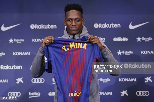 Barcelona's new Colombian defender Yerry Mina poses with his new jersey during a press conference in Barcelona on January 13 2018 / AFP PHOTO / Pau...
