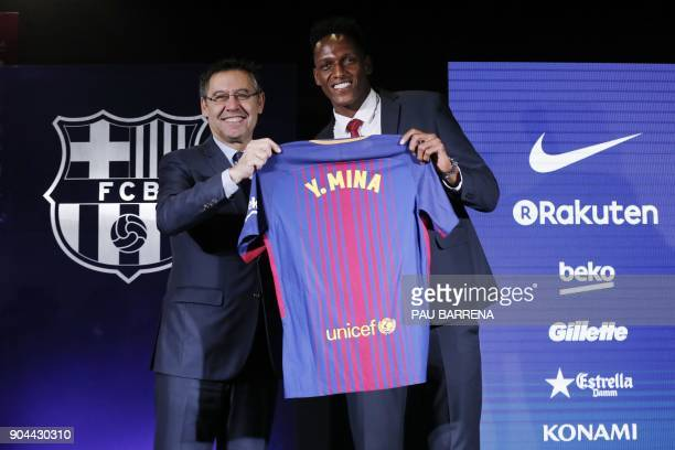 Barcelona's new Colombian defender Yerry Mina poses with his new jersey next to Barcelona football club president Josep Maria Bartomeu during his...