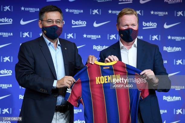 Barcelona's new Dutch coach Ronald Koeman poses with the president of the club Josep Maria Bartomeu during his official presentation at the Camp Nou...