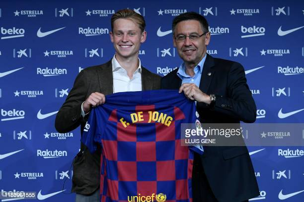 Barcelona's new Dutch midfielder Frenkie de Jong poses with his new jersey next to the football club's president Josep Maria Bartomeu during his...