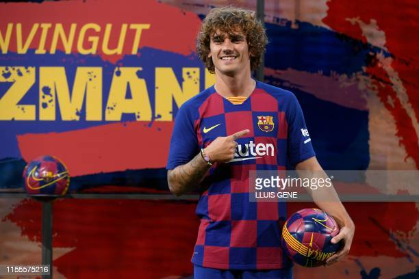 Barcelona's new French forward Antoine Griezmann poses with his new jersey during his official presentation by the Spanish football club at the Camp...