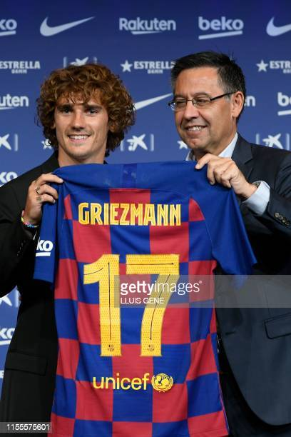 Barcelona's new French forward Antoine Griezmann poses with his new jersey next to the football club's president Josep Maria Bartomeu during his...