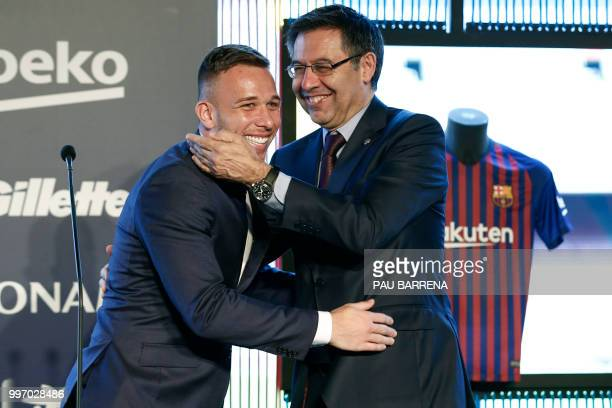 Barcelona's new player Brazilian midfielder Arthur Henrique Ramos de Oliveira Melo is hugged by Barcelona's president Josep Maria Bartomeu during his...