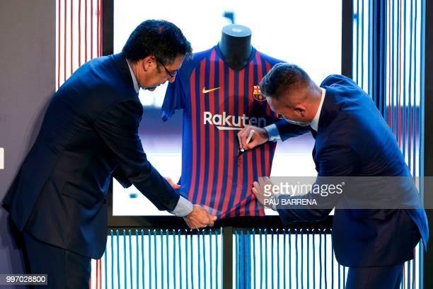 Barcelona's new player Brazilian midfielder Arthur Henrique Ramos de Oliveira Melo signs his new jersey next to Barcelona's president Josep Maria...