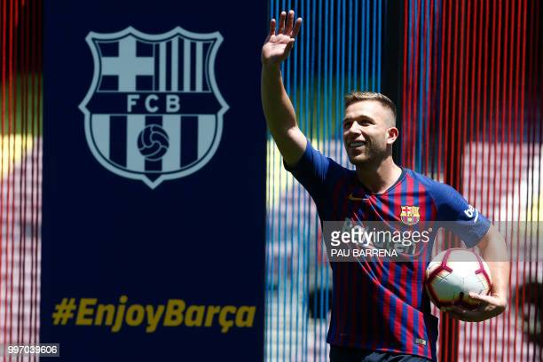 Barcelona's new player Brazilian midfielder Arthur Henrique Ramos de Oliveira Melo waves during his official presentation at the Camp Nou Stadium in...