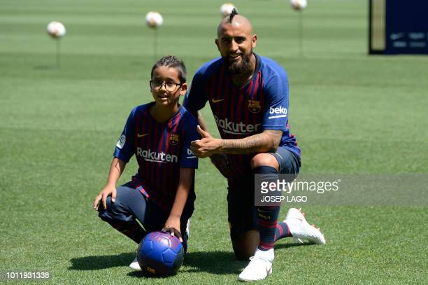 Barcelona's new player Chilean midfielder Arturo Vidal poses with his son Alonso during his official presentation at the Camp Nou stadium in...