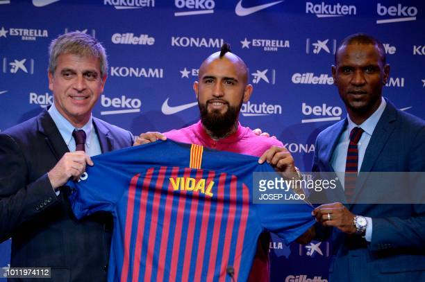 Barcelona's new player Chilean midfielder Arturo Vidal poses with Barcelona's technical secretary French Eric Abidal and Barcelona's vicepresident...