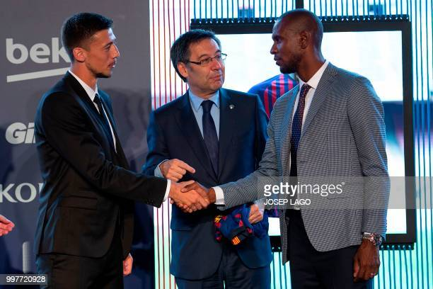Barcelona's new player French defender Clement Lenglet shakes hands with Barcelona's technical secretary French Eric Abidal next to Barcelona's...