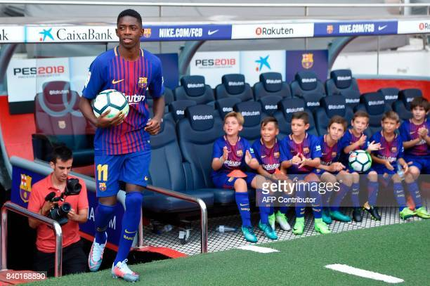 Barcelona's new player Ousmane Dembele enters the pitch past young fans at the Camp Nou stadium in Barcelona during his official presentation by the...