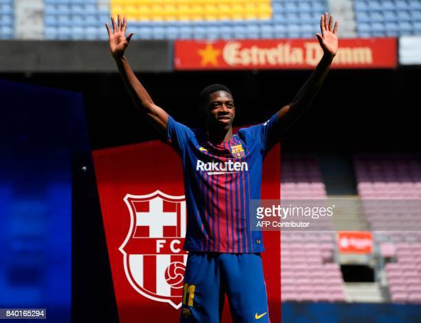 Barcelona's new player Ousmane Dembele gestures as he poses at the Camp Nou stadium in Barcelona during his official presentation by the Catalan...