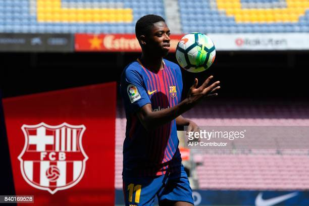 Barcelona's new player Ousmane Dembele plays with a ball as he poses at the Camp Nou stadium in Barcelona during his official presentation by the...