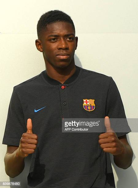 Barcelona's new player Ousmane Dembele poses outside the Camp Nou stadium in Barcelona prior to signing his new contract with the Catalan club on...