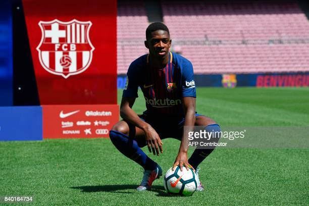 Barcelona's new player Ousmane Dembele poses with a ball at the Camp Nou stadium in Barcelona during his official presentation by the Catalan...