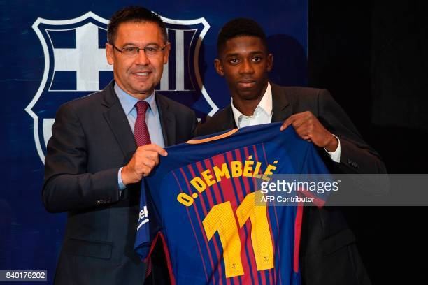 Barcelona's new player Ousmane Dembele poses with his new jersey next to Barcelona's president Josep Maria Bartomeu at the Camp Nou stadium in...