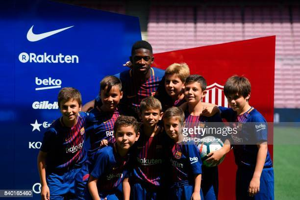 Barcelona's new player Ousmane Dembele poses with young fans at the Camp Nou stadium in Barcelona during his official presentation by the Catalan...