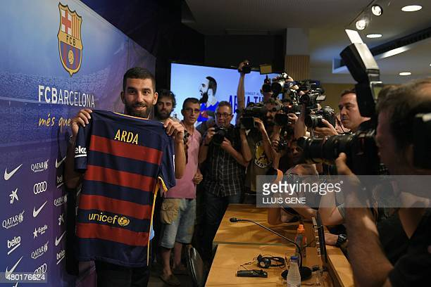 Barcelona's new player Turkish Arda Turan holds his new jersey at the Camp Nou stadium in Barcelona, after signing his new contract with the Catalan...