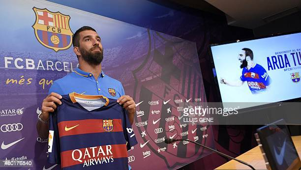 Barcelona's new player Turkish Arda Turan shows his new jersey at the Camp Nou stadium in Barcelona after signing his new contract with the Catalan...