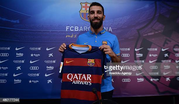 Barcelona's new player Turkish Arda Turan shows his new jersey during a press conference at the Camp Nou stadium in Barcelona after signing his new...