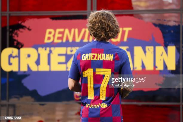 Barcelona's new sign French star Antoine Griezmann wearing Barcelona's traditional home jersey poses for a photo during his presentation ceremony at...
