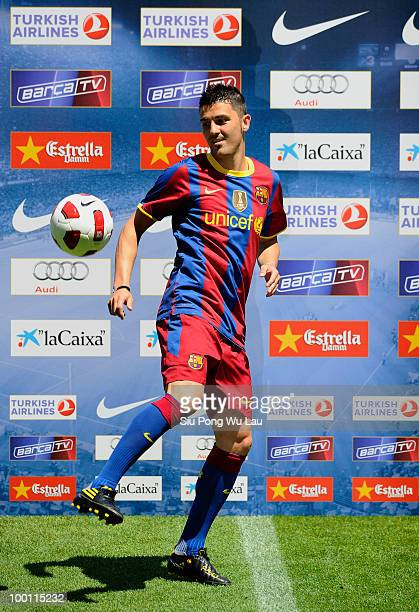 Barcelona's new signing David Villa juggles the ball as he poses for the cameras during his presentation at the Camp Nou stadium on May 21 2010 in...