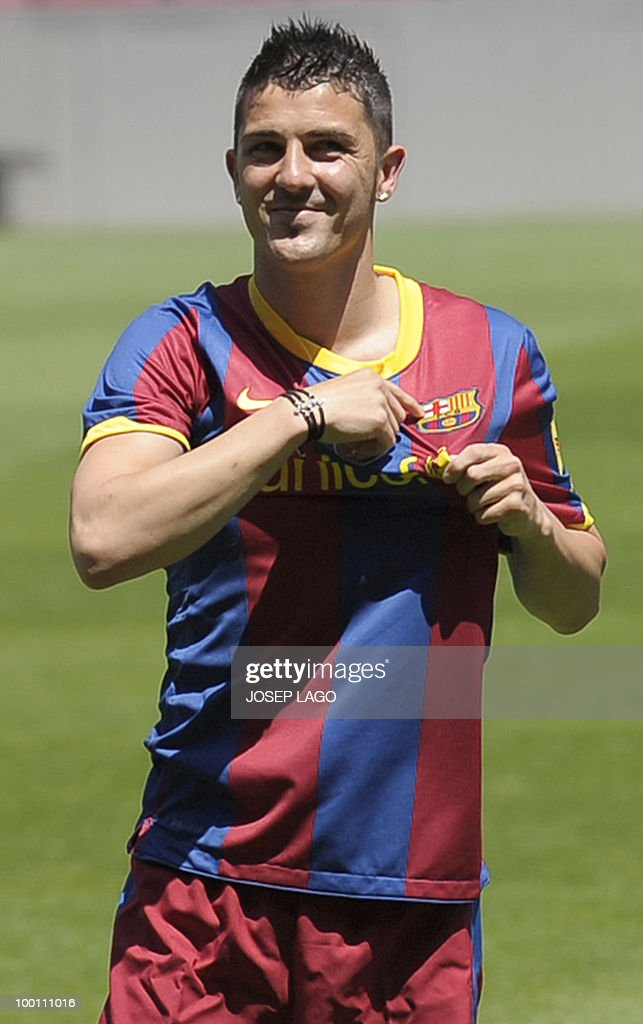 Barcelona's new signing David Villa smiles as he shows his new jersey of the Catalan giants in Barcelona on May 21, 2010. Barcelona have reached a deal to sign Spanish international striker David Villa for four years from cash-strapped Valencia for 40 million euros (49.4 million dollars) it was announced on May 19.