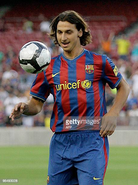 Barcelona's new signing Swedish striker Zlatan Ibrahimovic plays with a ball as he is wearing his new jersey after he signed a fiveyear contract with...