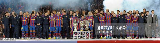 Barcelona's players and officials pose with the six trophies of the season 2009 before their Spanish League football match against Villarreal on...