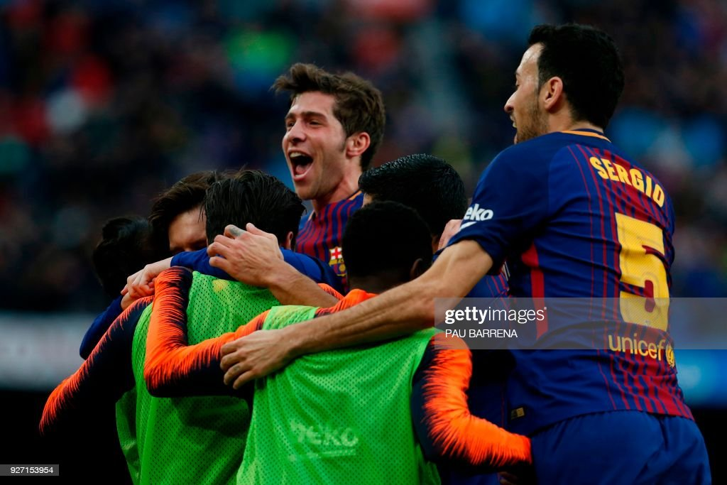 Barcelona's players celebrate after Argentinian forward Lionel Messi scored during the Spanish league football match FC Barcelona against Club Atletico de Madrid at the Camp Nou stadium in Barcelona on March 04, 2018. / AFP PHOTO / Pau Barrena
