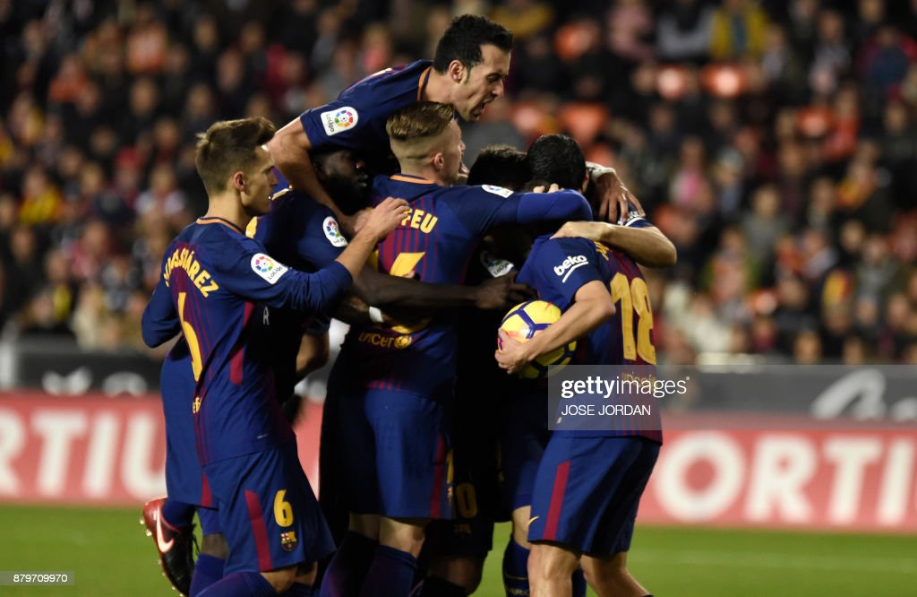 Barcelona's players celebrate after scoring during the Spanish league football match Valencia CF and FC Barcelona at Mestalla stadium in Valencia on November 26, 2017. /