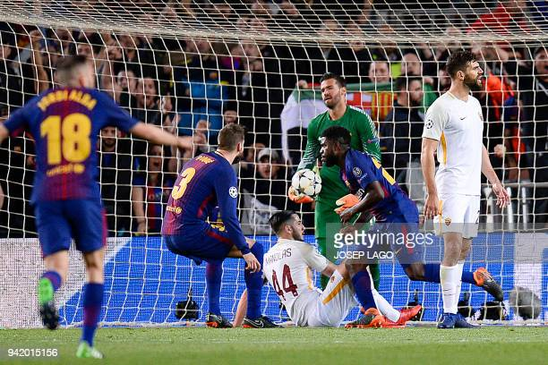 Barcelona's players celebrate past Roma's Brazilian goalkeeper Alisson as he reacts after Roma's Greek defender Kostas Manolas scored an own goal...