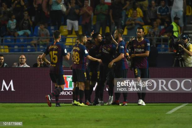 Barcelona's players celebrate with Barcelona's French forward Ousmane Dembele after his goal during the Spanish Super Cup final between Sevilla FC...