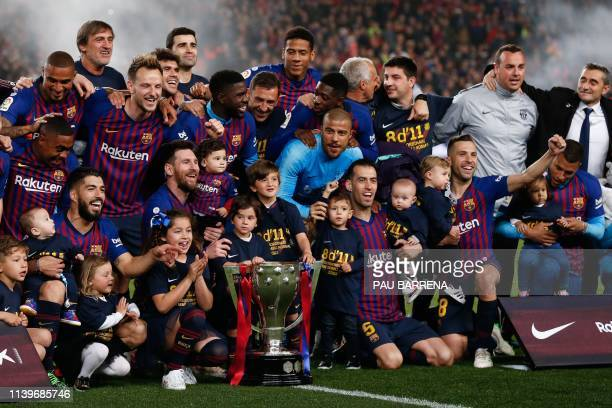 Barcelona's players celebrate with the Liga trophy after winning the club's 26th league title at the end of the Spanish League football match between...