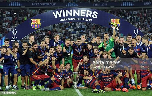 FC Barcelona's players celebrate with the trophy after winning the UEFA Super Cup final football match between FC Barcelona and Sevilla FC on August...