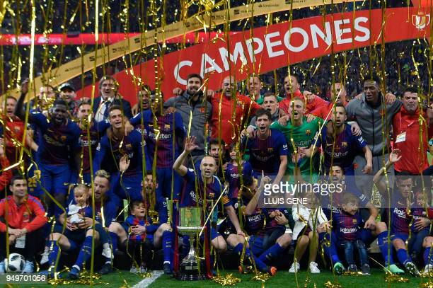 TOPSHOT Barcelona's players pose with the trophy after winning the Spanish Copa del Rey final football match Sevilla FC against FC Barcelona at the...